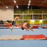 Acrobat Duo Perform Coordinated Flip Over Each Other