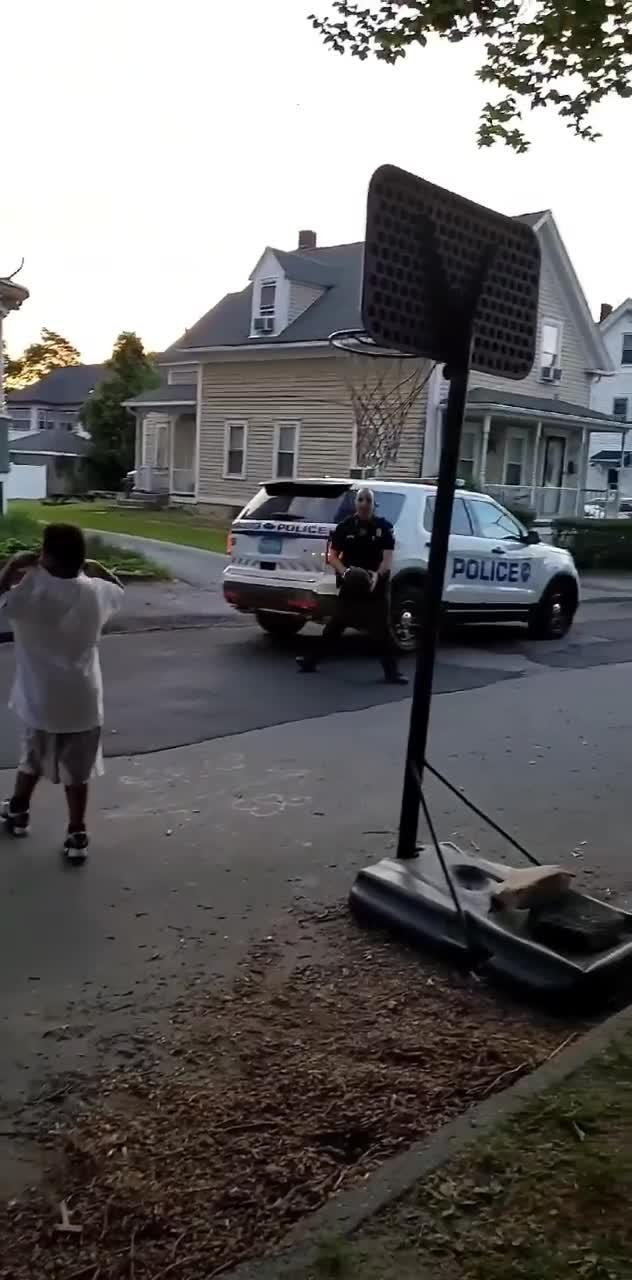 Boy Plays Basketball With Police Officer