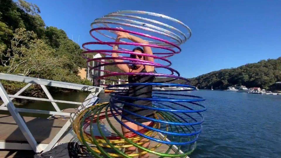 Girl Demonstrates Tricks With Rainbow Hula Hoop Slinky