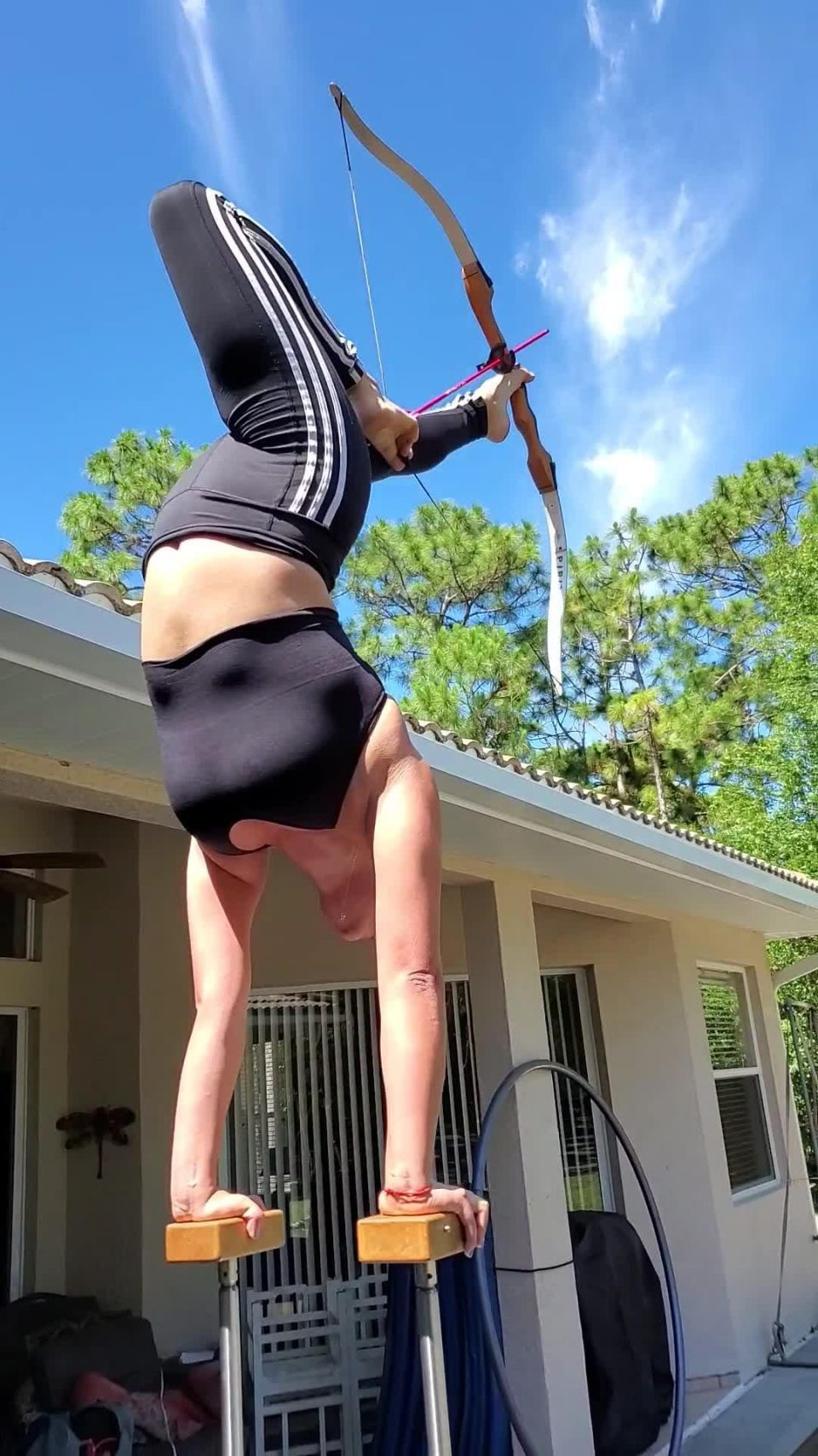 Girl in Handstand Position Fires Arrow at Target Using Toes