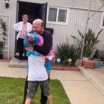 Grandpa Uses Plastic Sheet as Social Distancing Shield While Hugging Grandson