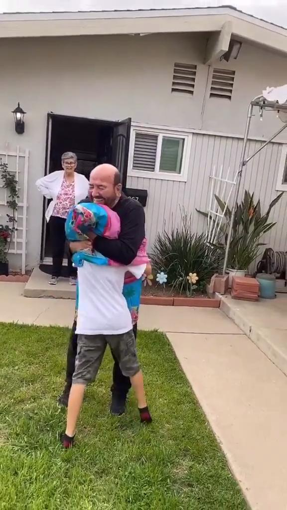Grandpa Uses Plastic Sheet as Social Distancing Shield While Hugging Grandson