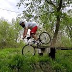 Guy Face Plants Into Ground As He Falls While Cycling Across Plank