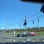 Guy Spotted Dancing on Top of Traffic Light