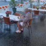 Man Finishes His Meal Sitting in Outdoor Restaurant Unfazed by Pouring Rain