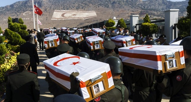 Turkish soldiers carry coffins during a mass burial ceremony for Turkish Cypriots who went missing in 1974 and whose remains have been found by the committee on missing people in Cyprus, on Aug. 15, 2016 at a cemetery