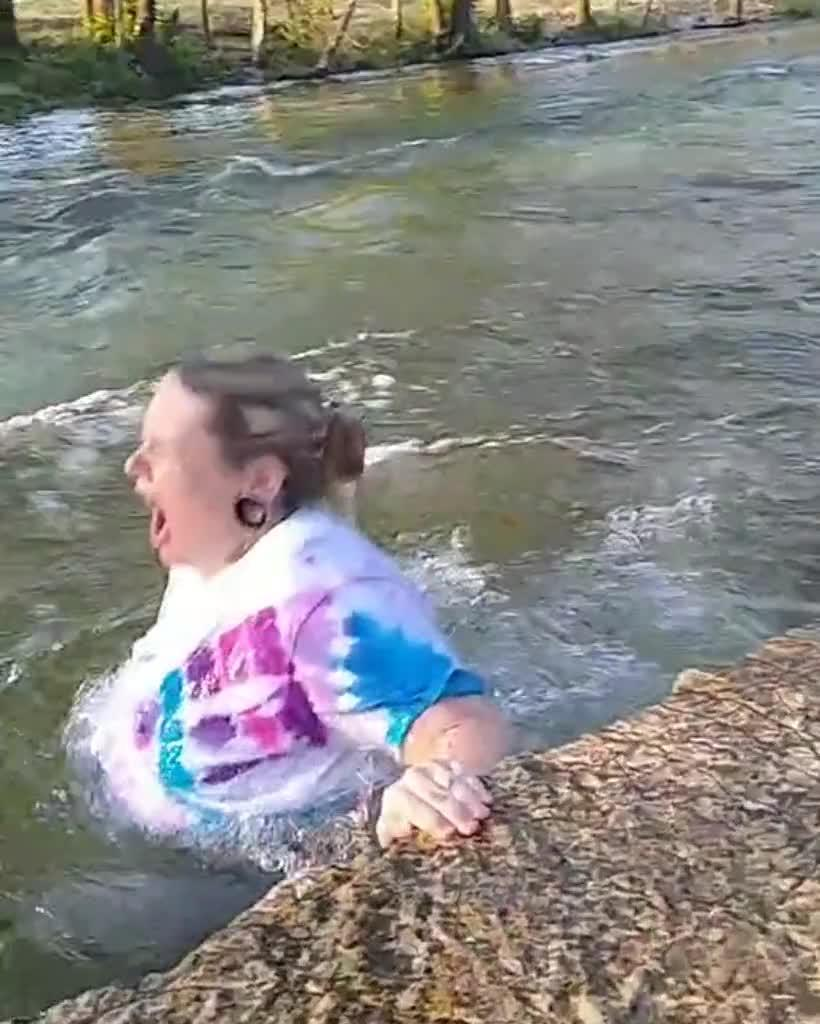 Woman Slips While Sitting and Posing on Rock and Falls in Water