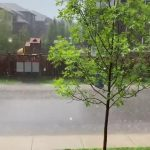 Trashcan Slides Down Roadside Water Stream During Rainstorm