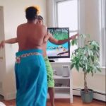 Two Men Wearing Towels do Hula Dance in Their Living Room While Sheltering in Place